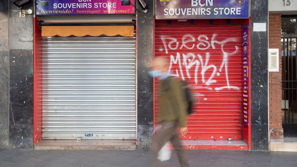 Foto: Un vecino pasa ante una tienda de recuerdos con la persiana bajada en Barcelona. (EFE)