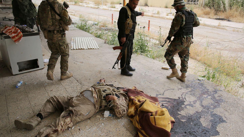 Combatientes peshmerga observan el cadáver de un militante del Daesh en Tel Asof, el 4 de mayo de 2016 (Reuters)