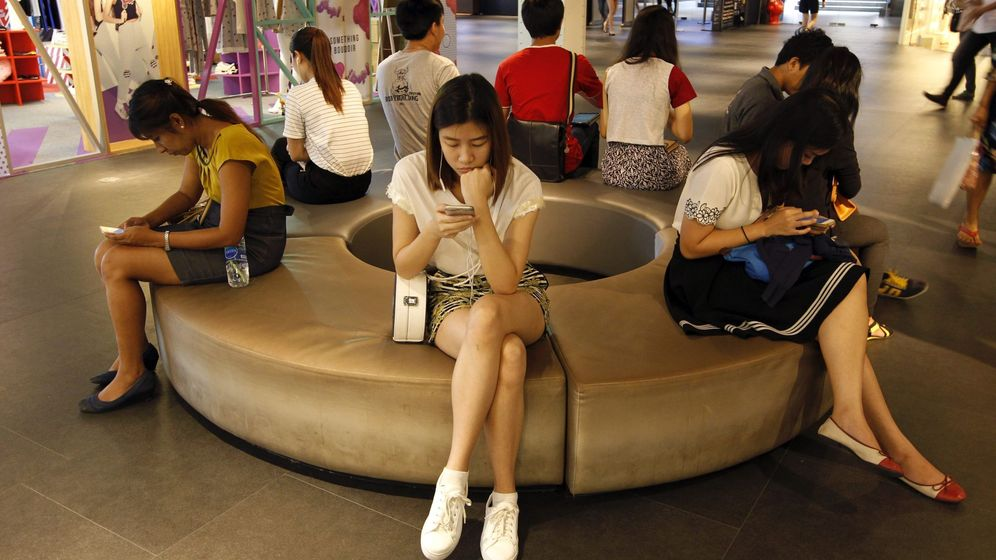 Foto: Tailandeses, leyendo en sus móviles. (EFE)