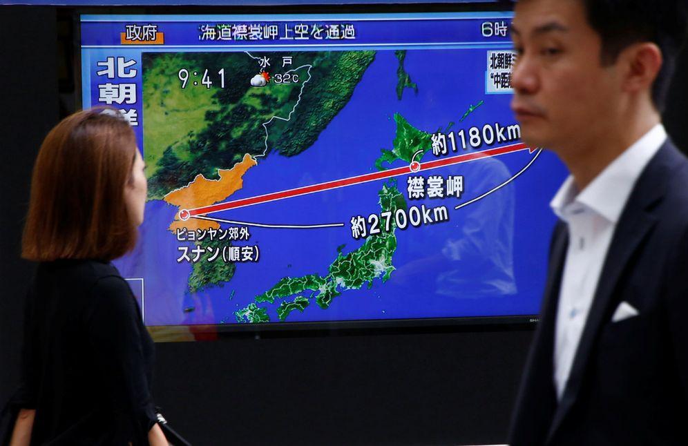 Foto: Japoneses pasan ante una pantalla de televisión que muestra el recorrido del misil norcoreano, en Tokio. (Reuters)