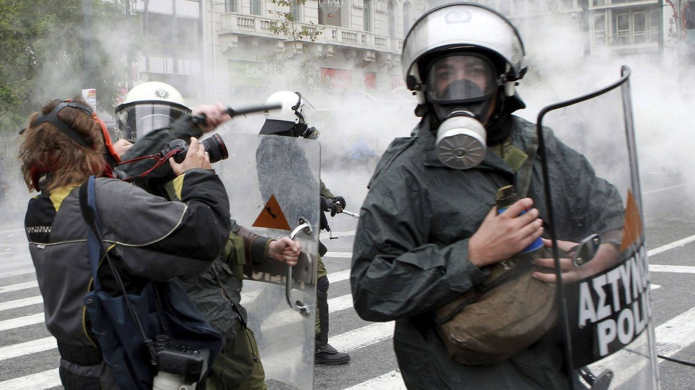 Agentes de policía golpean a un fotógrafo durante una protesta contra la Troika en Atenas (Efe).