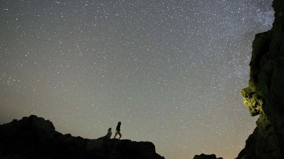 Foto: Dos personas observan la lluvia de estrellas de las Delta Acuáridas en una foto de archivo (EFE)