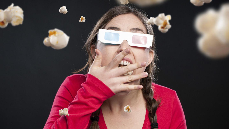 Una joven come palomitas durante una sesión de cine en 3D