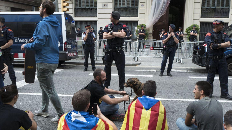 Los mossos d'Esquadra permanecen en guardia ante un grupo de jóvenes que protesta durante la huelga. (EFE)