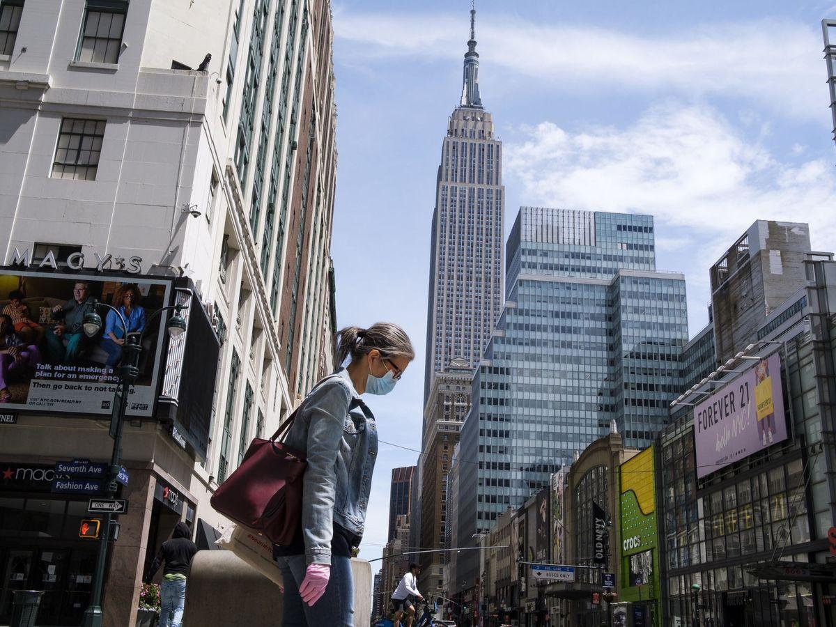 Foto: Una mujer con mascarilla camina por una calle de Nueva York. (EFE)