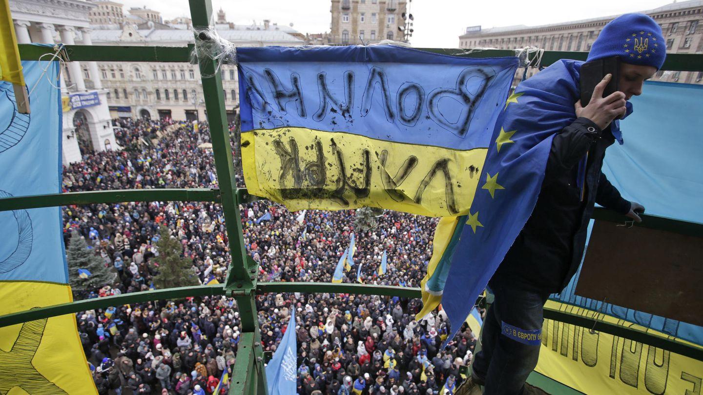 Un hombre encaramado a un árbol de Navidad artificial en la Plaza de la Independencia de Kiev, bastión del Maidán (Reuters).