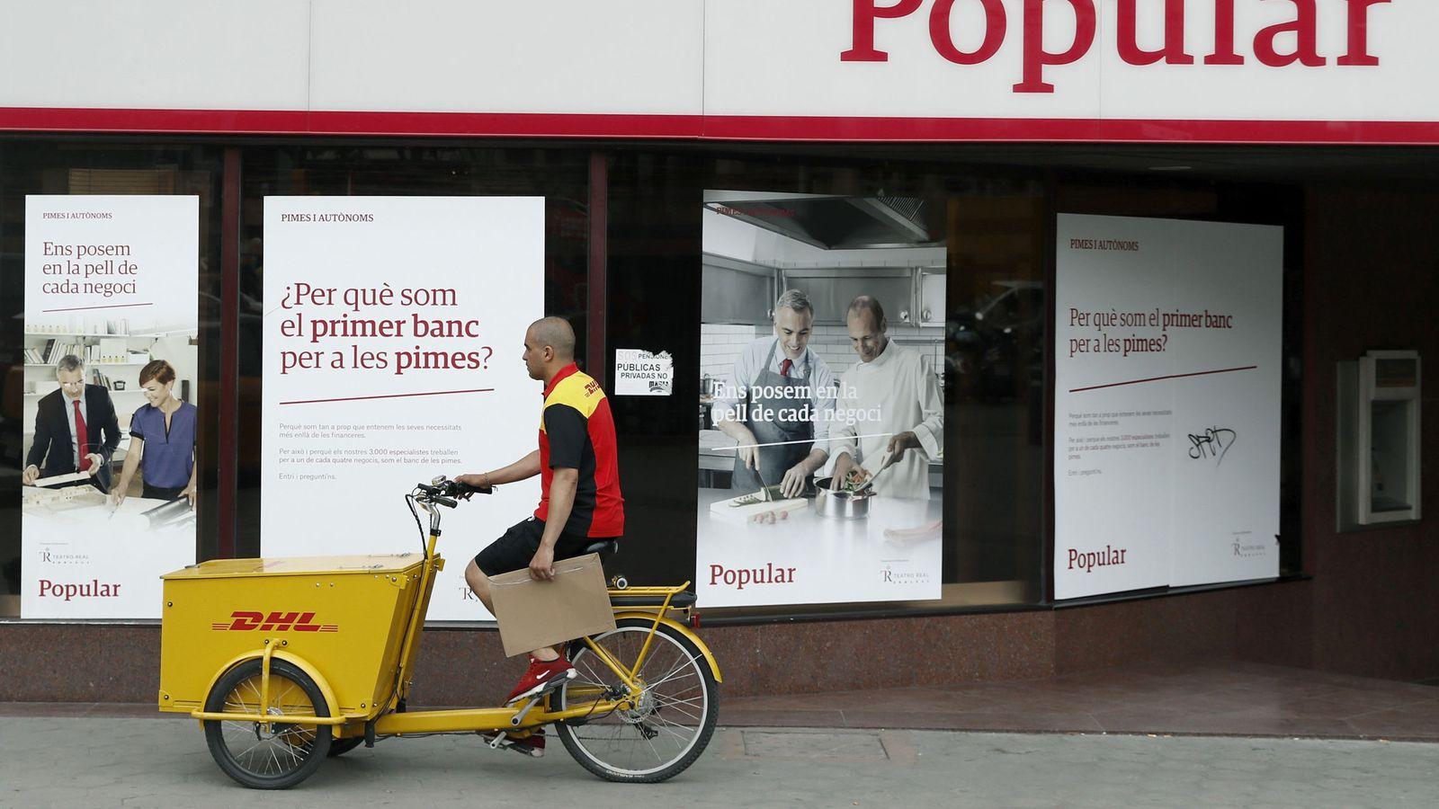 Foto: Un repartidor pasa ante una oficina del Banco Popular. (EFE)