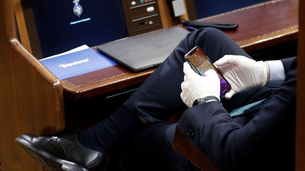 Foto: Un diputado consulta su móvil con unos guantes durante el pleno extraordinario para explicar la declaración del estado de alarma. (EFE)