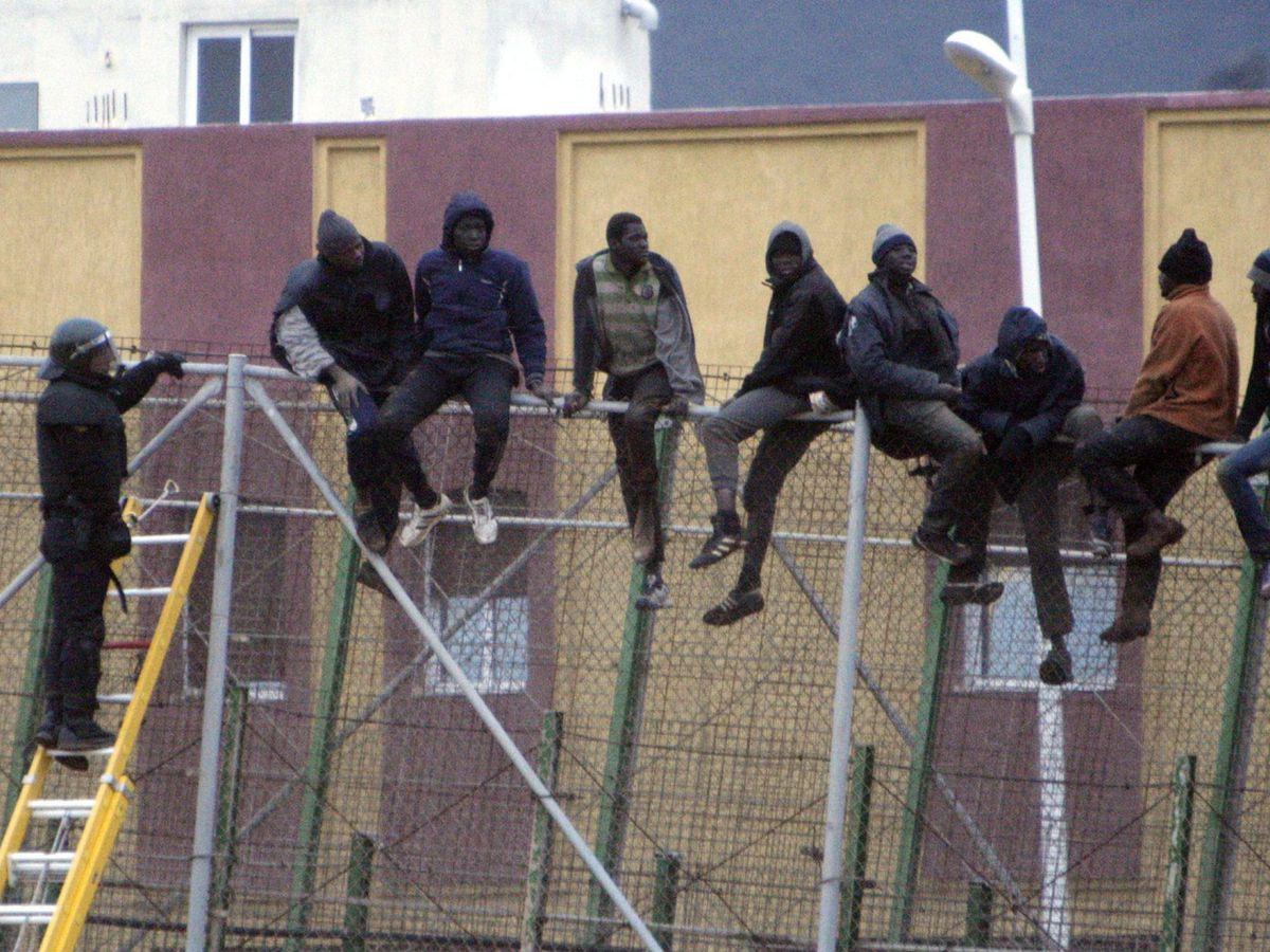 Foto: Una veintena de inmigrantes subidos a la valla de Melilla, en una imagen de 2015. (EFE)