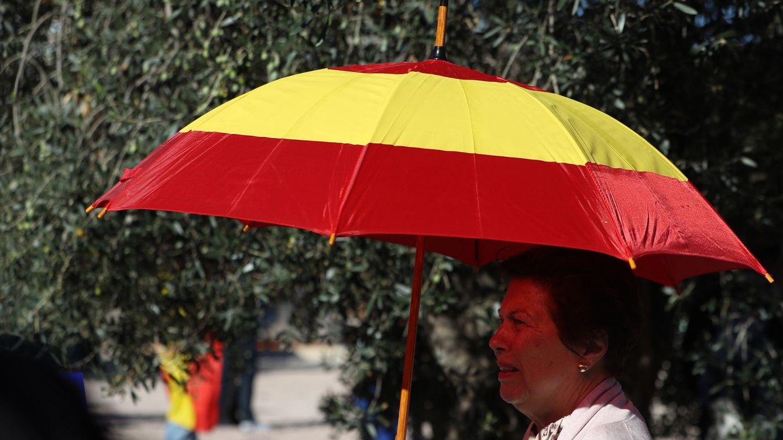 Foto:  Una mujer se protege del sol con un paraguas con la bandera de España. (EFE)