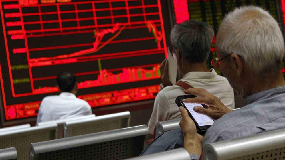 Foto: Un grupo de inversores mira una pantalla de cotizaciones en Pekín.