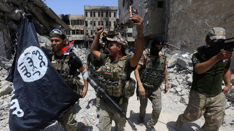 Efectivos del Ejército iraquí celebran la caída de Mosul con una bandera del Estado Islámico. (Reuters)