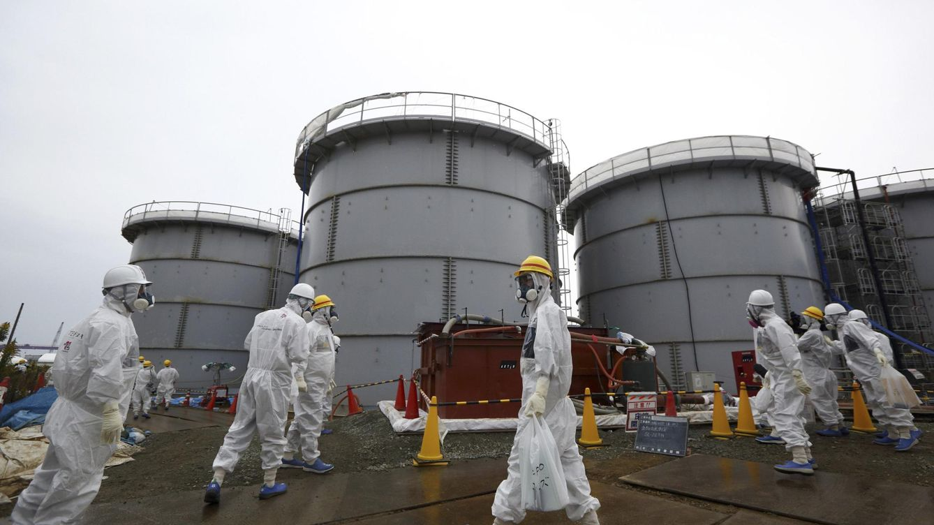 Foto: File photo of members of the media and tepco employees wearing protective suits and masks walking past storage tanks in fukushima prefecture