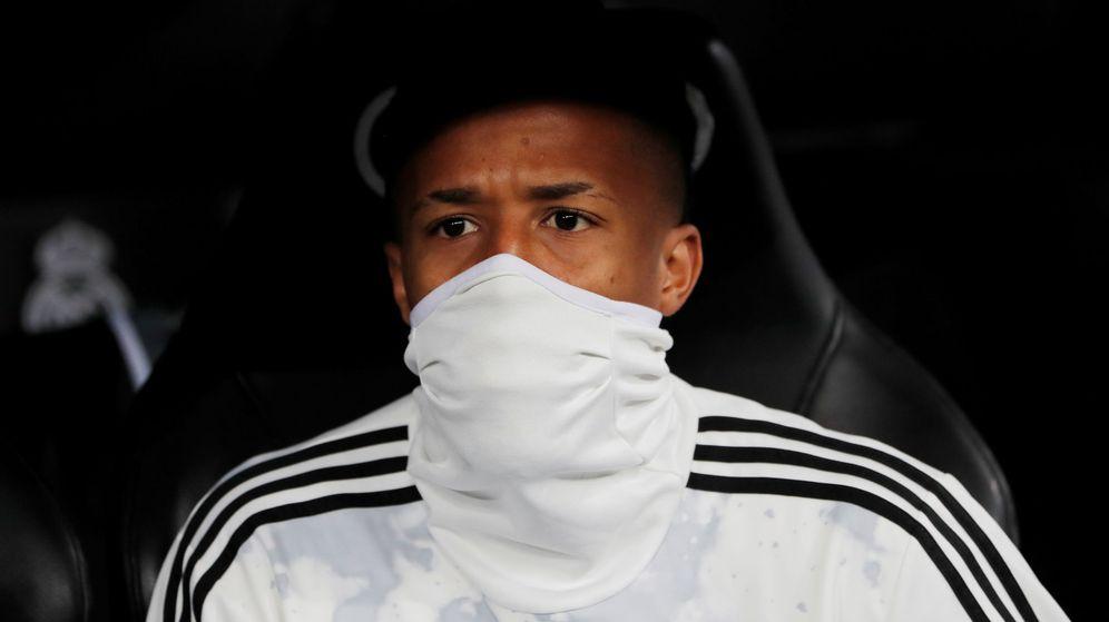Foto: Eder Militao en el banquillo del Bernabéu con la boca tapada. (Efe)