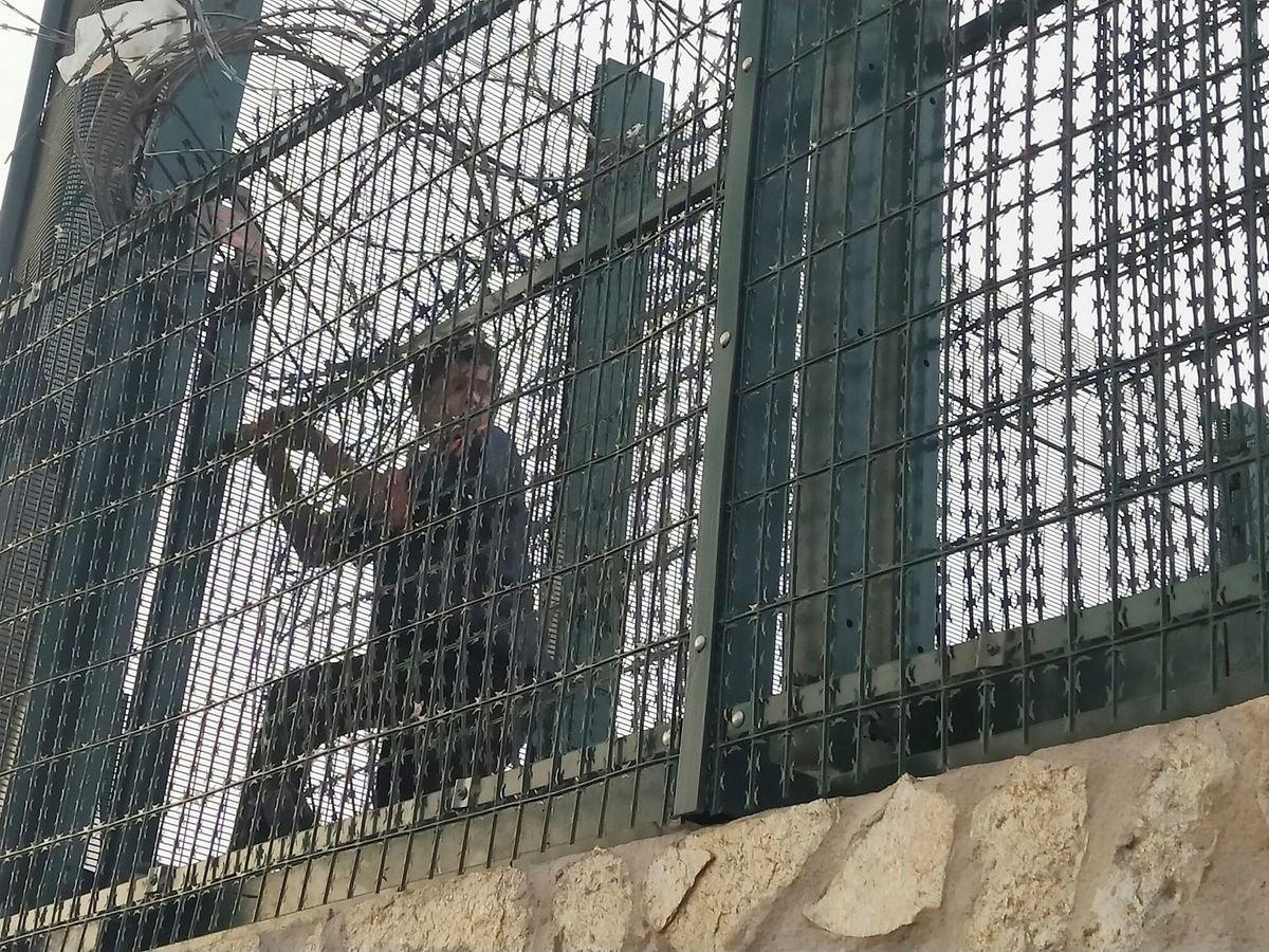 Foto: Un menor intenta acceder al puerto de Ceuta después de que saltara la noticia de las devoluciones. (EFE)