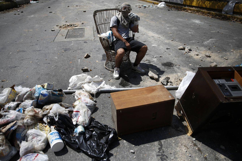 Foto: Un manifestante atichavista descansa tras enfrentamientos con las fuerzas de seguridad en Caracas (Reuters).