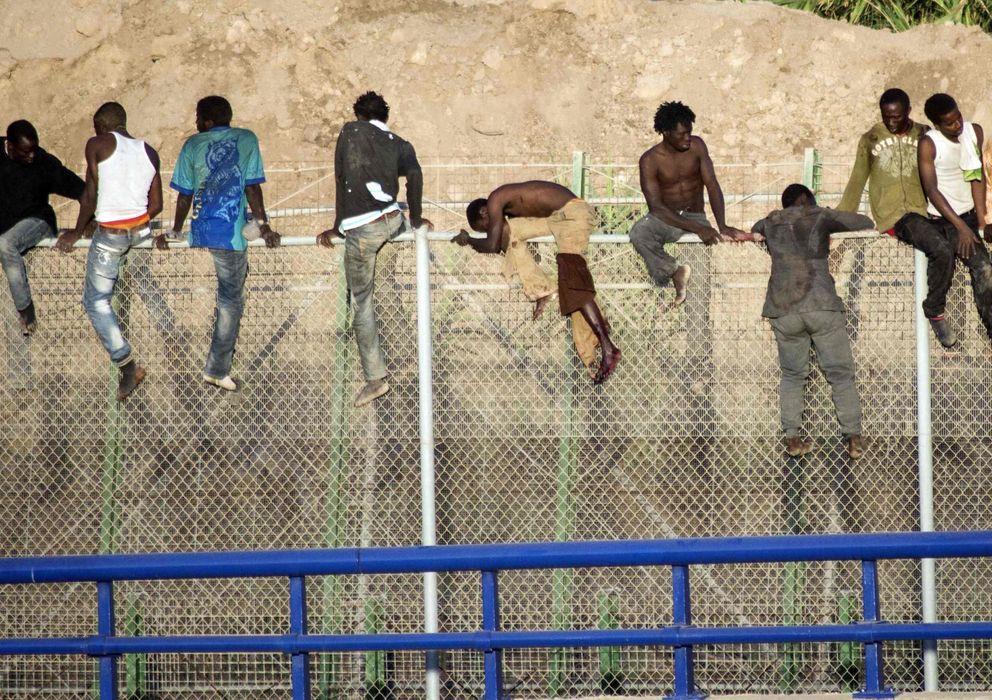 Foto: Varios subsaharianos saltan la valla de Melilla (Efe)