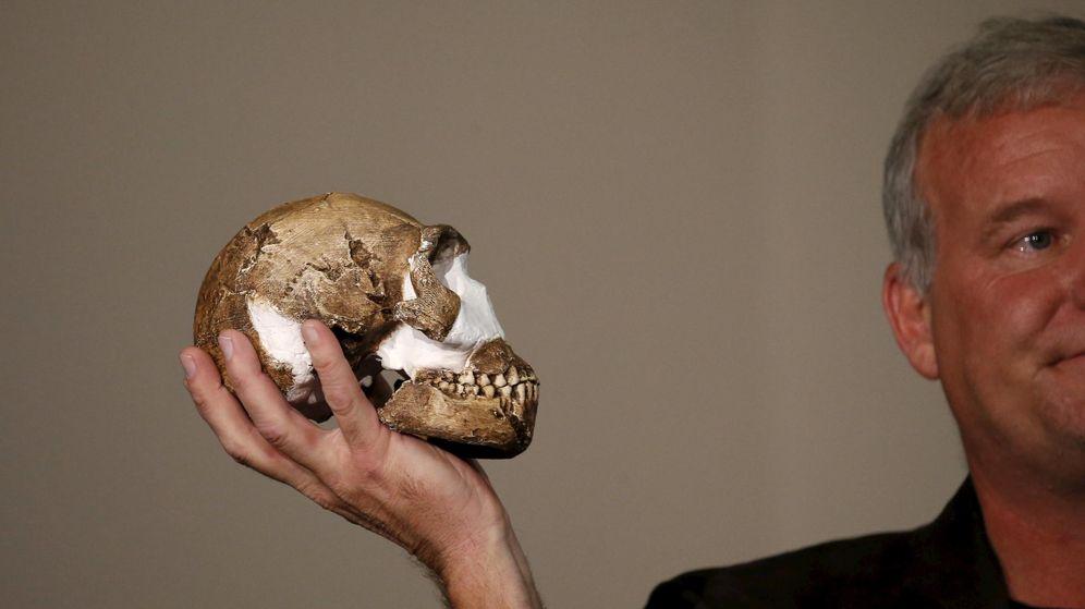 Foto: Lee Berger sostiene una réplica del cráneo del nuevo homínido