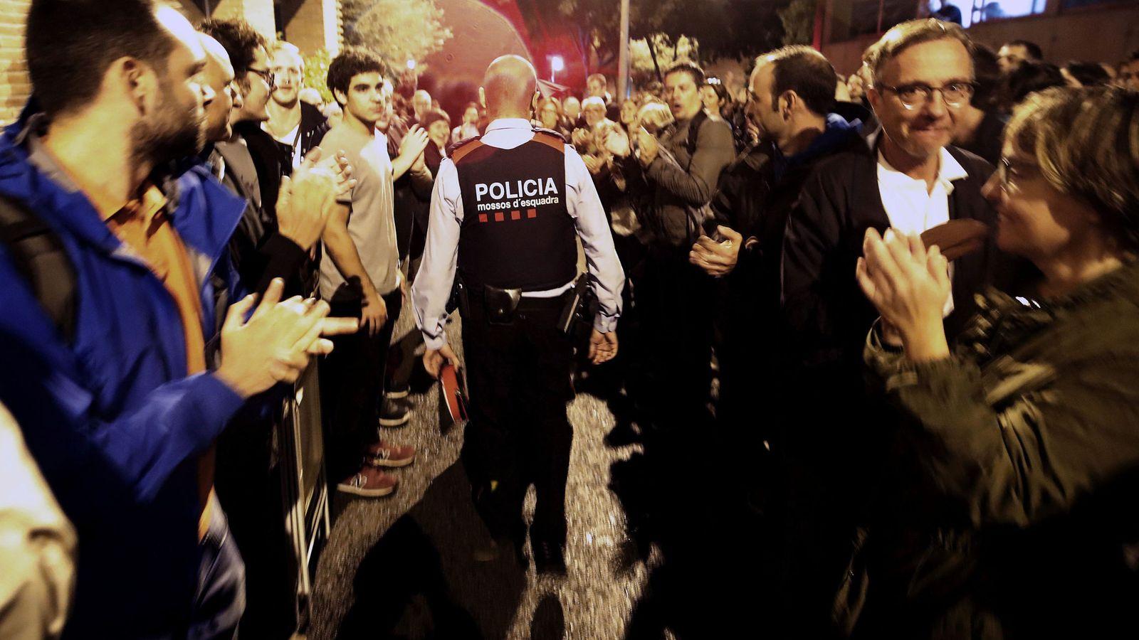 Foto: Una pareja de Mossos d'Esquadra salen entre aplausos de una escuela del barrio de Sarriá de Barcelona el 1-O. (EFE)