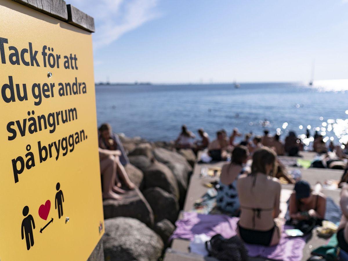 Foto: Un cartel con información sobre el covid-19 en una playa en Malmo, Suecia. (EFE)