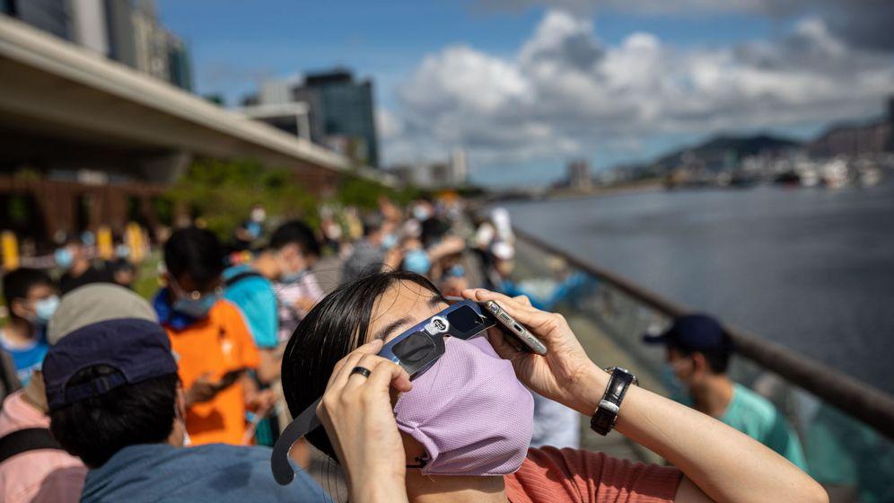 Foto: Astrónomos amateur contemplan el eclipse de sol parcial en Hong Kong (EFE)