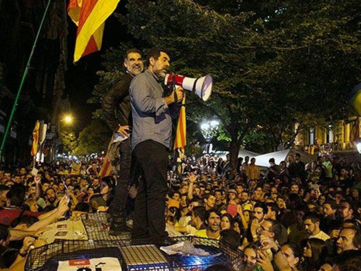 Foto: Jordi Sánchez y Jordi Cuixart sobre un coche de la Guardia Civil durante los sucesos de octubre de 2017 en Barcelona (EFE)