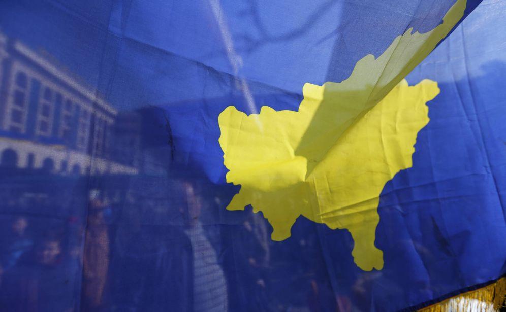 Foto: Varias personas tras una bandera de Kosovo durante las celebraciones del décimo aniversario de la independencia, en Pristina. (Reuters)