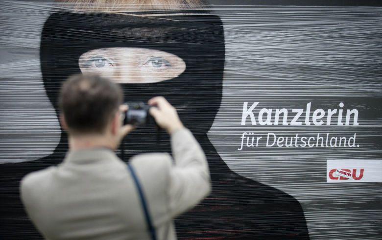 Un hombre saca una foto a un cartel electoral con el rostro de Merkel cubierto con pintura negra tras un acto vandálico en Berlín (Efe).