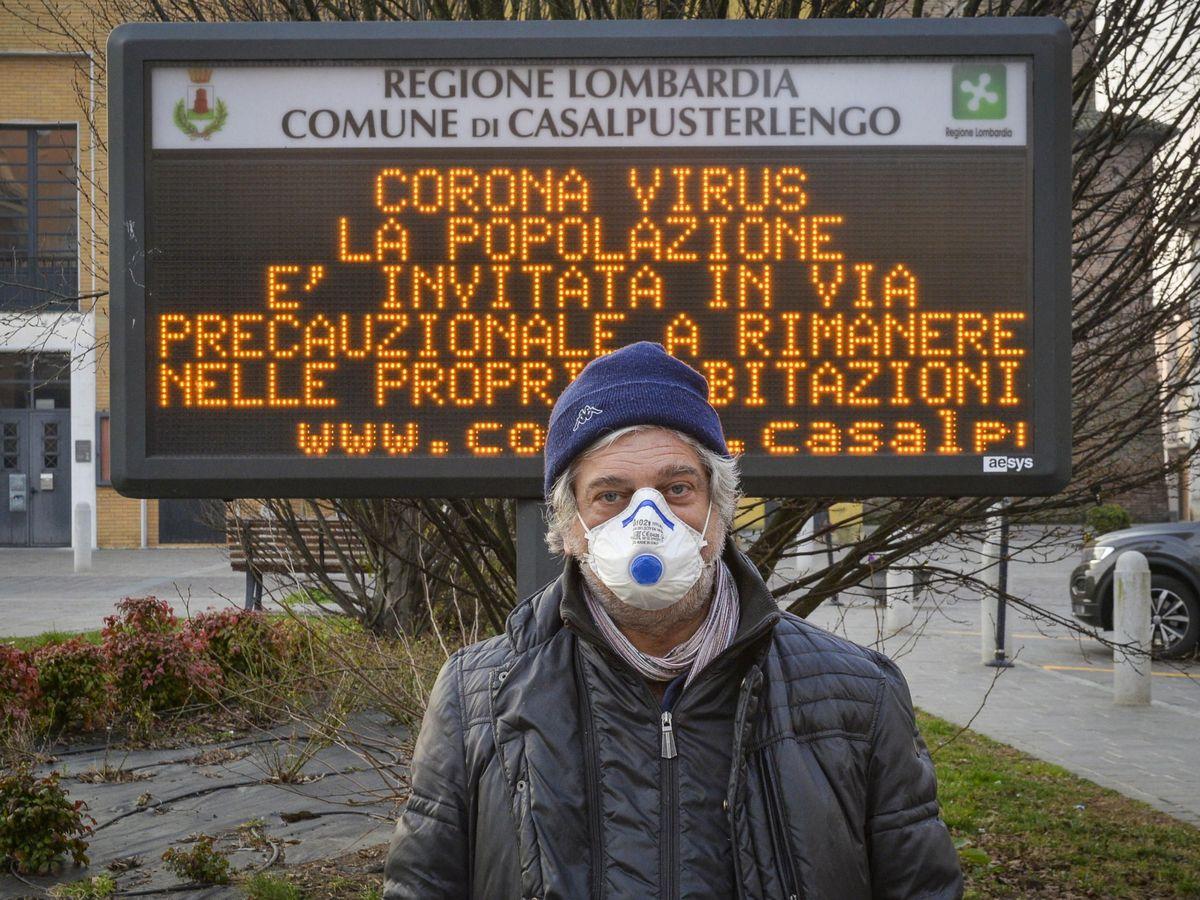 Foto: Un hombre con mascarilla posa ante un cartel que alerta del coronavirus en Casalpusterlengo. (EFE)