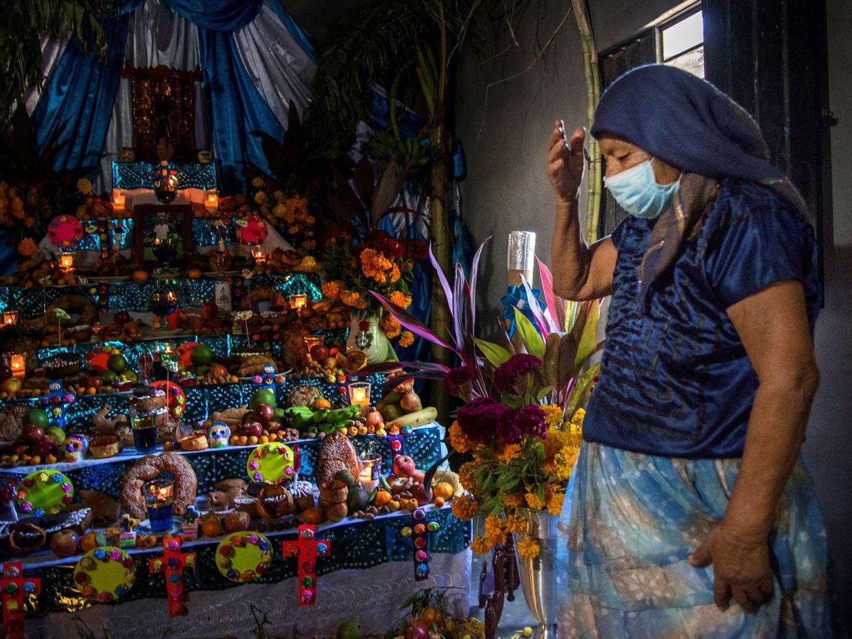Foto: Una mujer reza frente a su altar de Día de Muertos. (EFE)