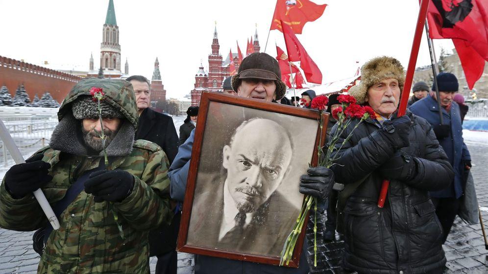 Foto: Varias personas marchan con banderas del partido comunista y una fotografía de Lenin. (EFE)