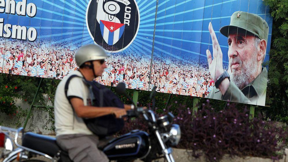 Foto: Un motociclista pasa frente a un cartel con la imagen de Fidel Castro, en La Habana (Cuba).