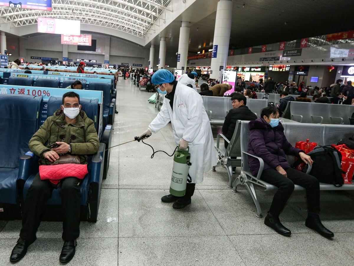Foto: Operarios desinfectan una zona de espera de una estación en China. (EFE)