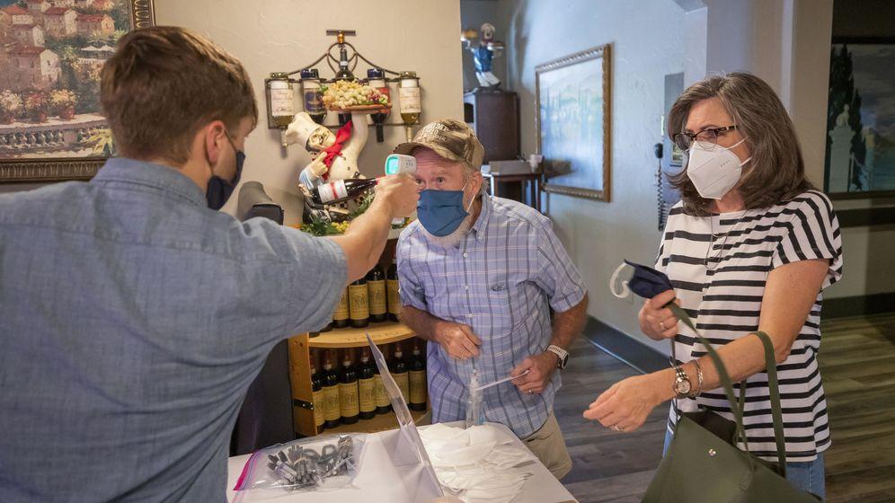 Foto: Un joven toma la temperatura a unos asistentes a un mitin en Georgia. (EFE)