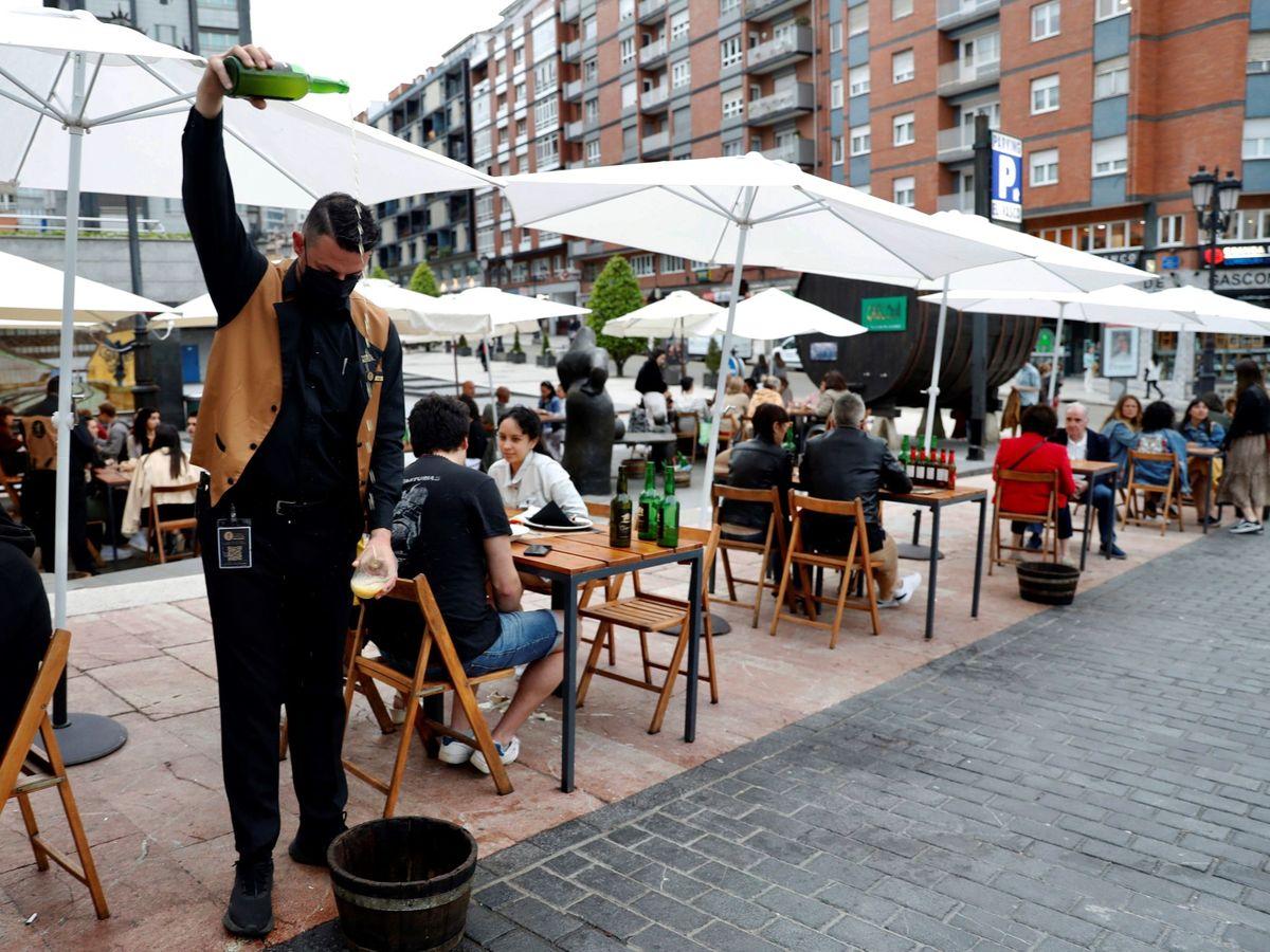 Foto: Un camarero escancia sidra en una terraza de la calle Gascona de Oviedo. (EFE)