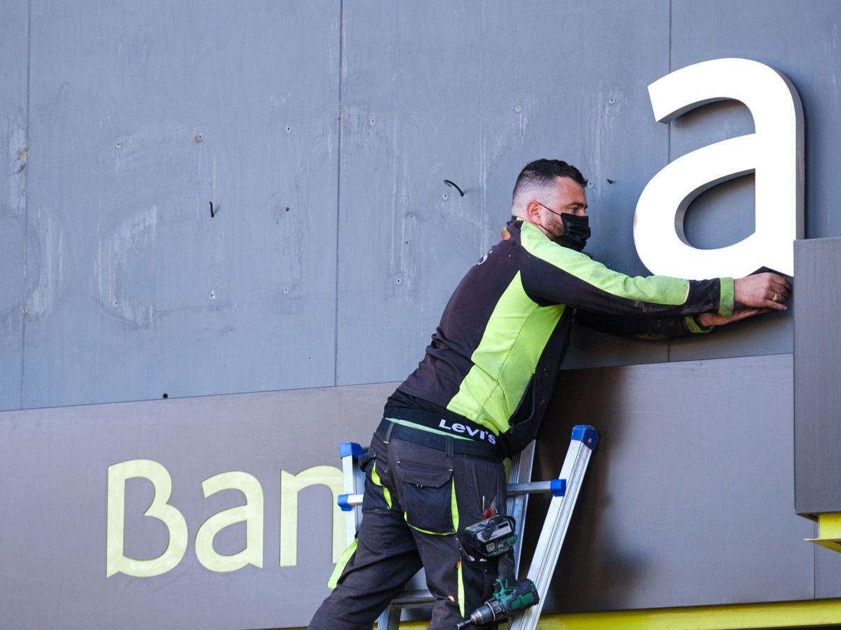 Foto: Un operario desmonta el rótulo de Bankia en su sede tras la fusión con CaixaBank (EFE)