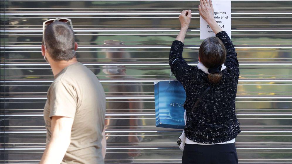 Foto: Una mujer coloca un aviso en la persiana cerrada de un negocio del centro de Oviedo. (EFE)