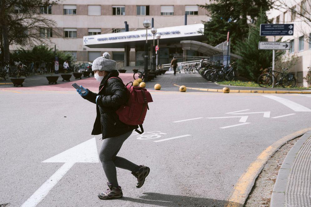 Foto: Una persona camina con mascarilla por el acceso al hospital de Txagorritxu. (EFE)