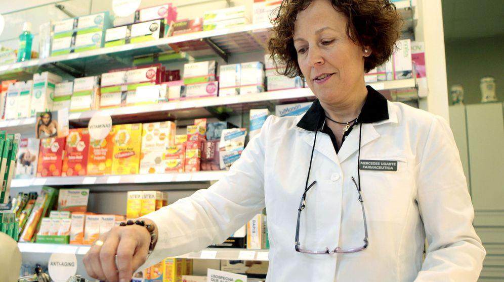 Foto: Una farmacéutica pasa la tarjeta sanitaria para realizar el copago en el País Vasco (EFE)