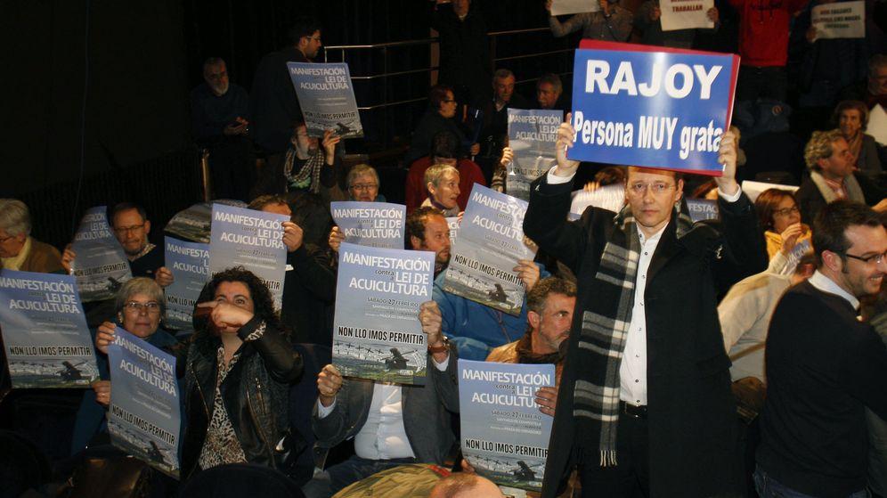 Foto: Un asistente al pleno muestra una pancarta de apoyo a Mariano Rajoy. (Efe)