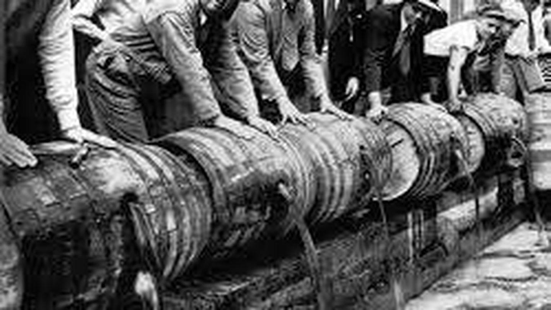 Hombres tirando alcohol de los barriles.