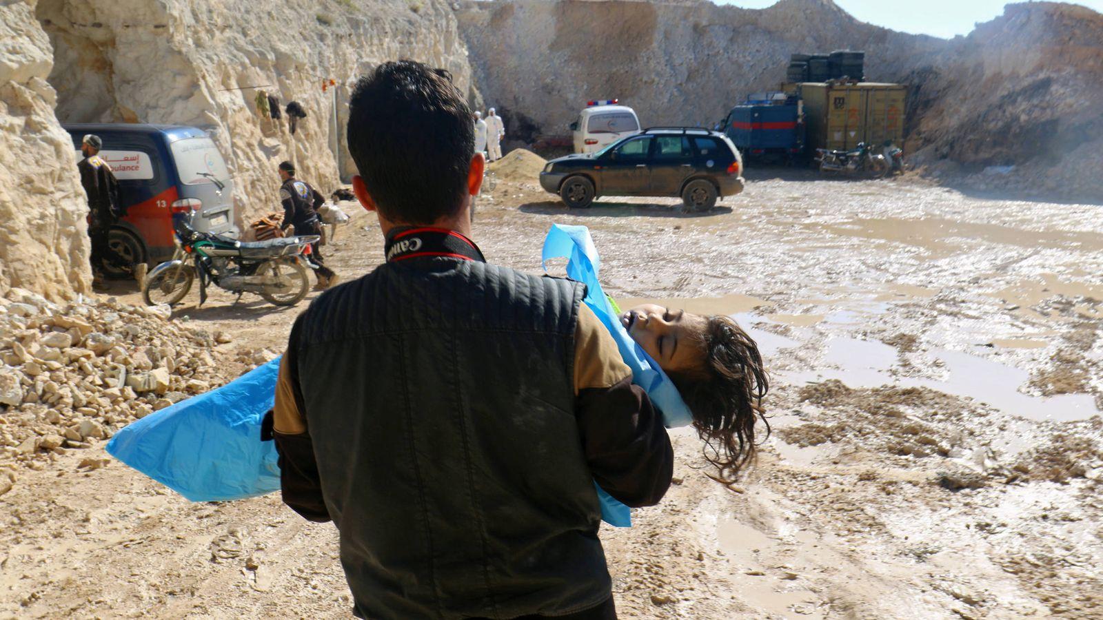 Foto: Un hombre carga con el cadáver de un niño tras un ataque químico en el pueblo de Jan Sheikun, en la zona rebelde de Idlib. (Reuters)