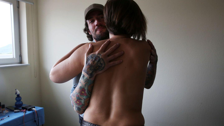 Un tatuador que trabaja con personas que han pasado por un cáncer abraza a Mamen Malagon tras tatuarle un pezón en su pecho reconstruido después de una mastectomía. (Reuters)