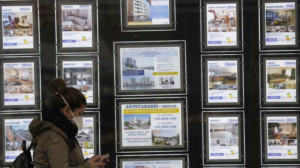Foto: Una mujer pasa por delante de un portal inmobiliario de venta y alquiler en Bilbao. (EFE)