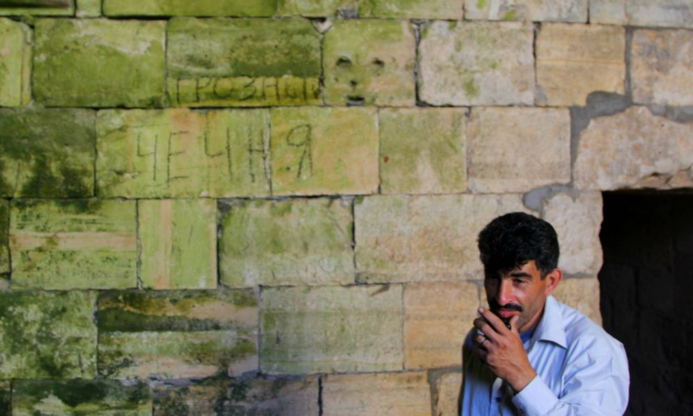 Foto: Sadri, el sirio que custodia el Crac de los Caballeros. Tallado en la pared, un mensaje de los yihadistas: Grozni. Chechenia. (Ángel Martínez)