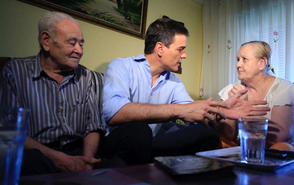 Foto: Pedro Sánchez, con Mercedes y Ramón, la primera familia que visitó en su puerta a puerta en un inmueble del centro de Móstoles, en Madrid. (EFE)