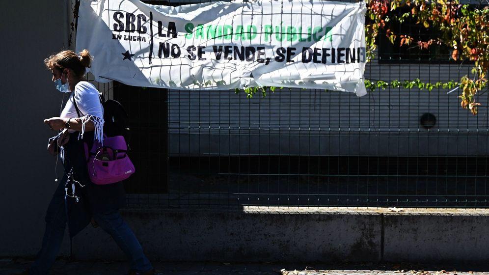 Foto: Una mujer pasa ante un cartel de defensa de la Sanidad pública en Madrid. (EFE)