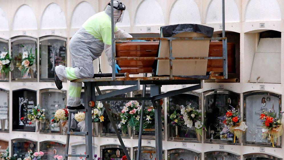 Foto: Un operario introduce un féretro en el cementerio de Santa Margarida de Montbui (Barcelona). (EFE)