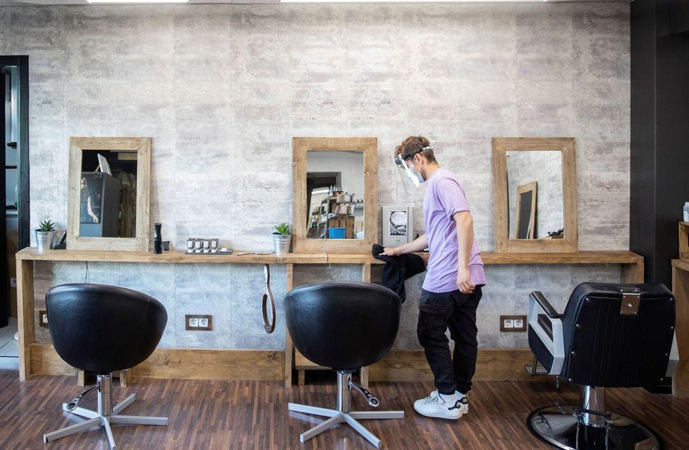Foto: Un empleado desinfecta la zona de corte de una peluquería de Madrid, este 2 de mayo. (EFE)