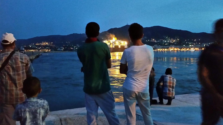 Dos refugiados sirios observan los ferris que parten hacia el Pireo desde la isla de Lesbos. (Foto: P. Cebrián)